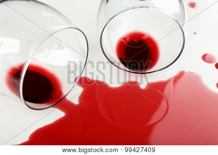 Spilled wine from glasses on white background