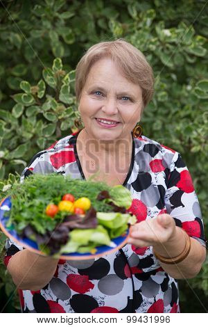 Happy pensioner woman with vegetables at dacha