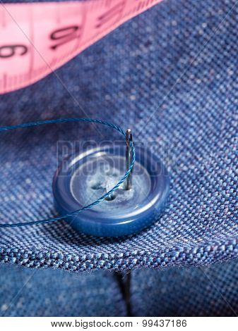 attaching of button to blue silk suit by needle close up poster