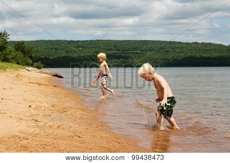 Two brothers a lboy and his little brother are playing on the beach on the shore of Lake Superior in Wisconsin poster