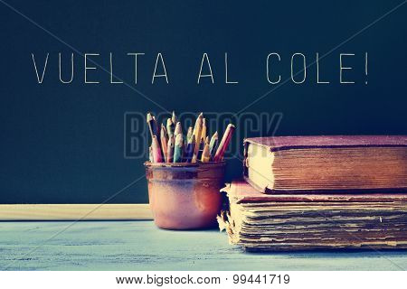 some pencils in a pot, some old books on a blue school desk, and the text vuelta al cole, back to school in Spanish written on a chalkboard, with a filter effect
