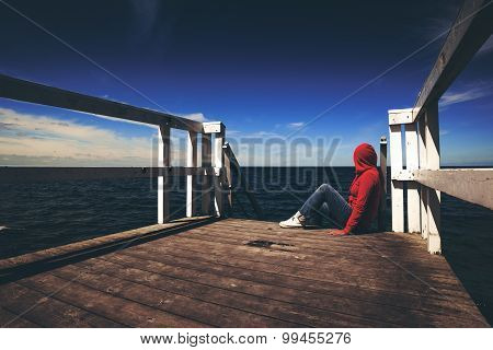 Alone Young Woman in Red Hooded Shirt Sitting at the Edge of Wooden Pier Looking at Water - Hopelessness Solitude Alienation Concept Retro Toned poster