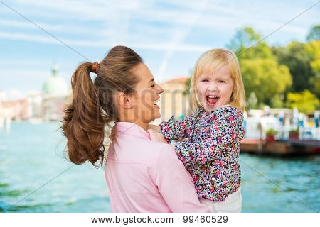 Laughing Mother In Profile Holding Happy Daughter In Venice