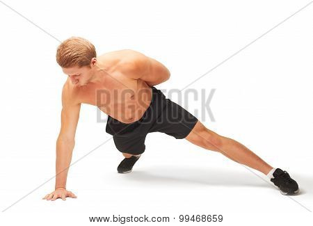 Young muscular handsome shirtless sportsman doing push-ups on one arm isolated on white background poster