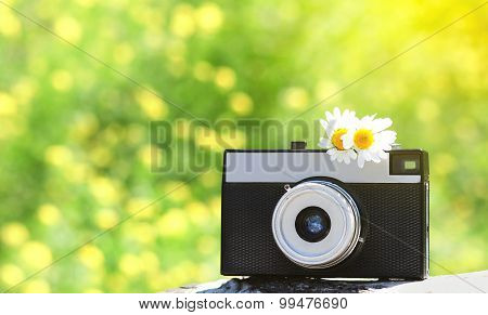 Retro Old Vintage Camera With Chamomiles Flowers Over Sunny Summer Bokeh Background