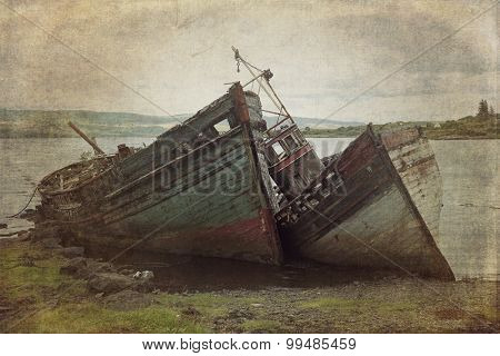 Two old wooden boats aground on isle of Mull, Scotland.  Cross processed to look like an instant picture with texture.
