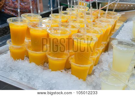 Fresh Orange Juice In Plastic Glasses On A Bed Of Ice
