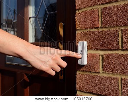 Woman Extends Her Hand To Ring Doorbell