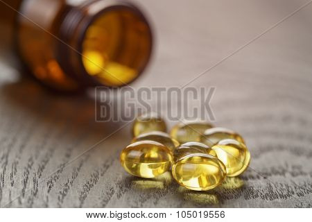fish oil capsules on wooden tabe