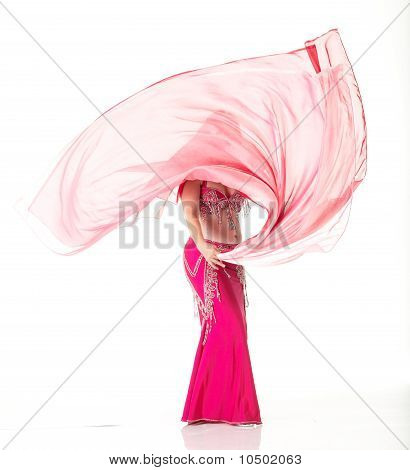 Lithe adult caucasian belly dancer with red hair and pink belly dancing outfit performing a dance with veils on a white background. Not Isolated poster