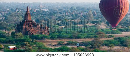 Temple and hot air balloon flying over Bagan