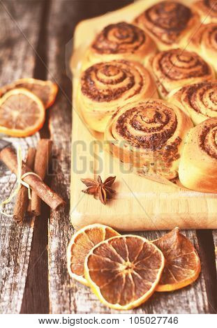 Cinnamon pastry on the wooden table with cinnabon stick toned photo