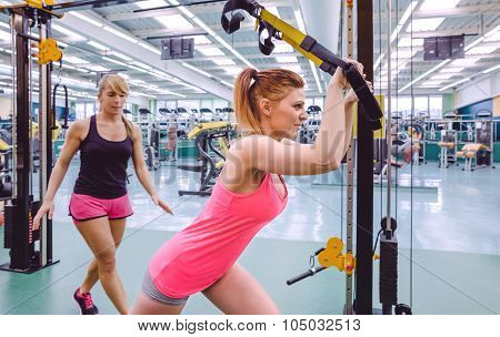 Female personal trainer helping to woman in a suspension training with fitness straps on a fitness center poster