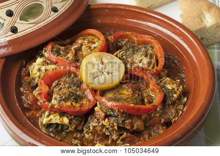 Moroccan fish tagine with chermoula, red peppers and preserved lemon close up