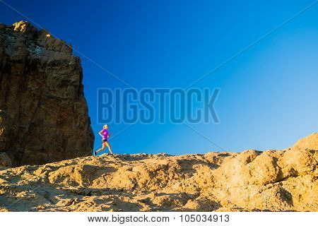 Woman Trail Running On Rocky Mountains