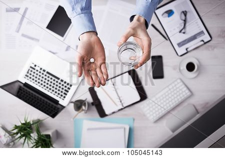 Office worker taking a pill and holding a glass of water hands close up with desktop on background top view poster