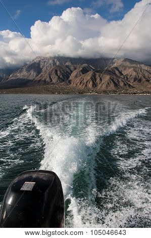 Boat wake in sea with mountains in background