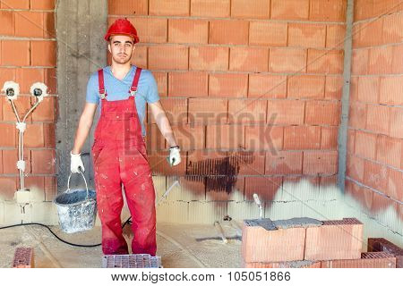 Brickmason Working On Construction Site, Worker On Building Site.