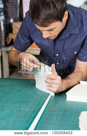 Mid adult male worker binding pages at table in paper factory
