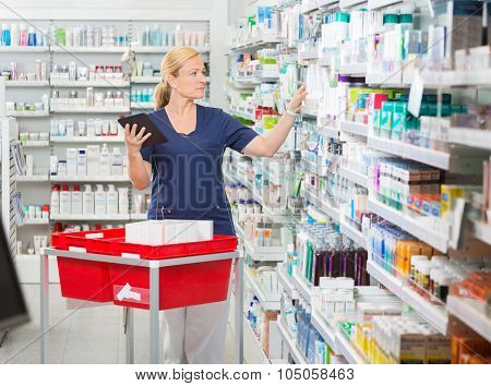 Mature female pharmacist updating stock in digital tablet at pharmacy