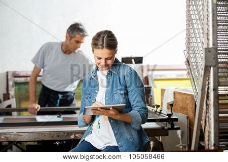 Mid adult female worker using digital tablet while colleague working in background at paper factory