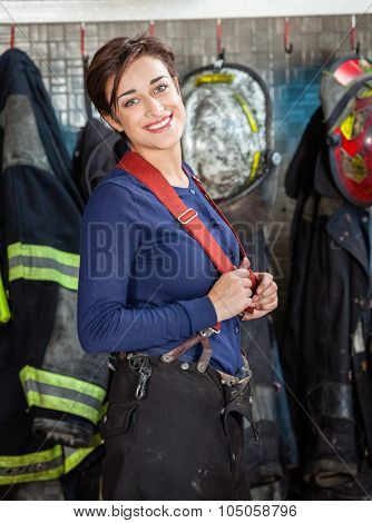 Portrait of happy young firewoman standing at fire station