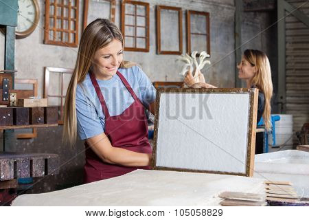 Happy mid adult female worker looking at dried paper on mold in factory poster