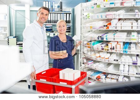Portrait of happy female assistant and male pharmacist arranging products in pharmacy