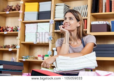 Thoughtful mid adult saleswoman leaning on stacked papers in shop