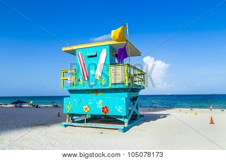 People Enjoy The Beach Next To A Lifeguard Tower