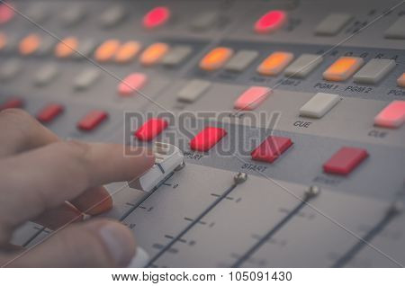 hand on the fader audio console