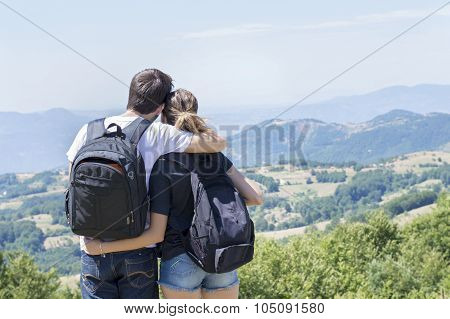Couple Of Hikers With Backpacks Standing At Viewpoint And Enjoying A View
