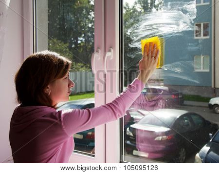 young brunette woman in pink blouse washing a window pane with yellow rag poster