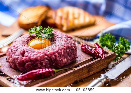 Raw beef .Tasty Steak tartare. Classic steak tartare on wooden board. Ingredients: Raw beef meat salt pepper egg garlic chilli herb decoration and toast bread poster