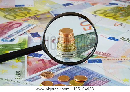 Coin Stack Behind Magnifying Glass