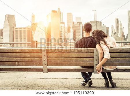 Couple Relaxing On New York Bench In Front Of The Skyline At Sunset Time. Concept About Love,relatio