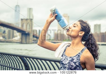 Thirsty athlete drinking after long run in New york city. Brooklyn bridge and skyline in the background poster
