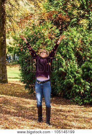 Woman enjoying the fall leaves