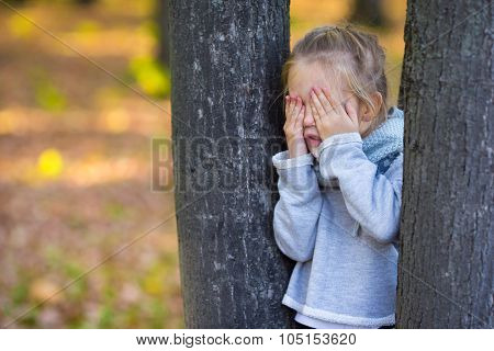 Little girl playing hide and seek near the tree in autumn park
