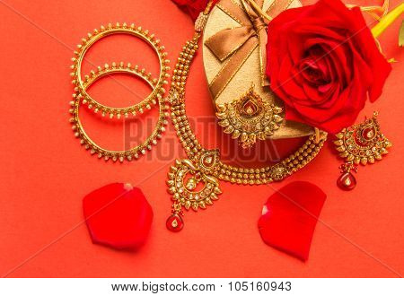 Classic design of an Indian gold necklace and bangles set arranged with heart shaped gift box and red rose flowers.