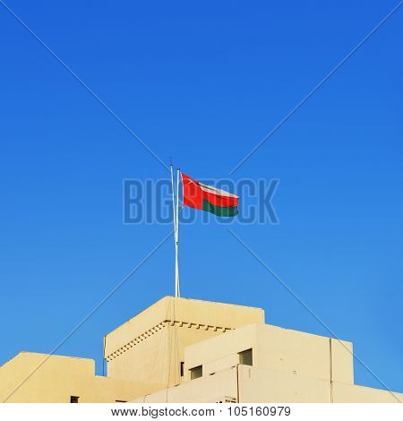 National flag of Oman is hoisted on the building in the city of Muscat.
