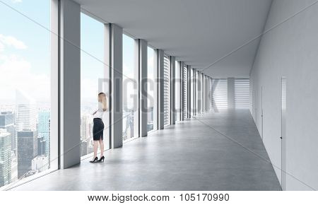 A Woman In Formal Clothes Is Looking Out The Window. Empty Modern Bright Clean Interior Of An Open S