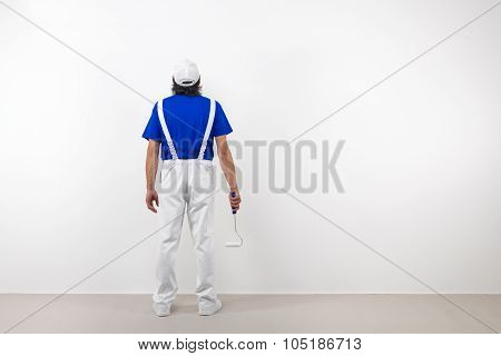 Painter With Paintroller Looks At White Wall