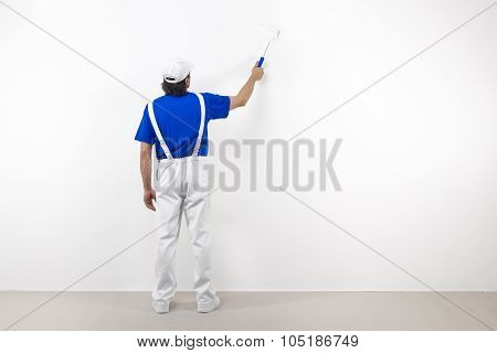 Painter With Paintroller On White Wall