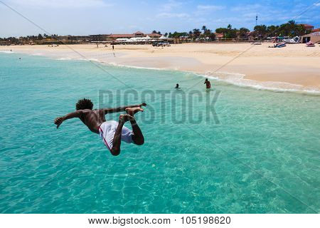 Teenage Cape Verdean Boy Jumping On The Turquoise  Water Of Santa Maria Beach In Sal Cape Verde - Ca