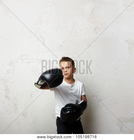 Young boxer wearing white tshirt and shows his jab on the concrete wall background.