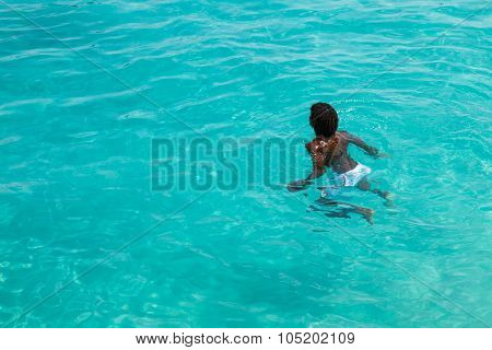 Teenage Cape verdean boy swimming on the turquoise water of Santa Maria beach in Sal Cape Verde - Cabo Verde poster