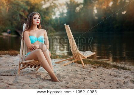 Girl Is Sitting Deck Chair Beach Near The Lake.
