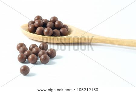 Wooden Spoon Full Of Herbal Cough Lozenges On White