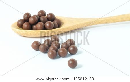 Wooden Spoon Full Of Herbal Cough Lozenges On A White Background